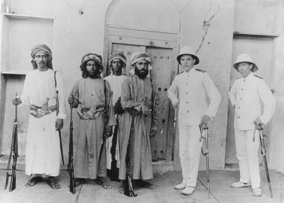 Photograph of Seyid Nada, Theyab, Taimur Sultan of Oman, C H Heath-Caldwell and Mr Webber taken Wednesday 22nd April 1914 at Barka Birka Castle on the North East coast of Oman
